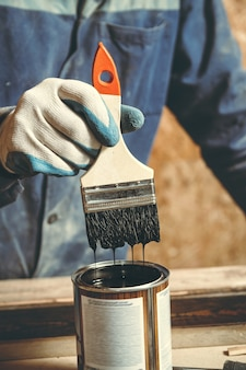 A man paints a handmade wooden product with paint in a workshop