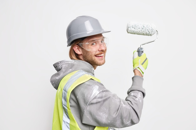 Man paints new home holds roller wears protective helmet glasses and uniform does repair poses on white