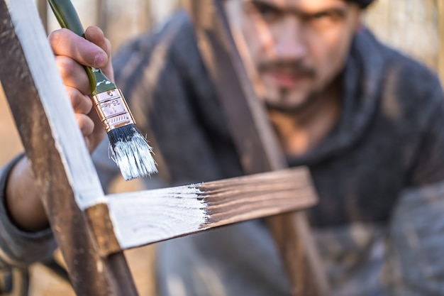 A man paints with white paint on wooden planks. man in industrial concept. there is a place for text, the object is close up.