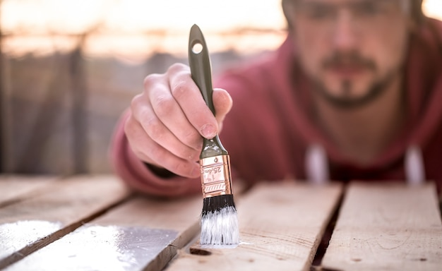 Man paints with white paint on wooden planks