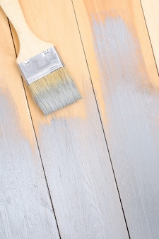 A man paints wooden boards in gray paint brush.