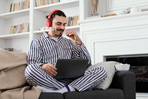 Man in pajamas spending fun time on laptop