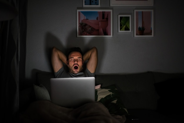 Man in pajamas with a computer yawning