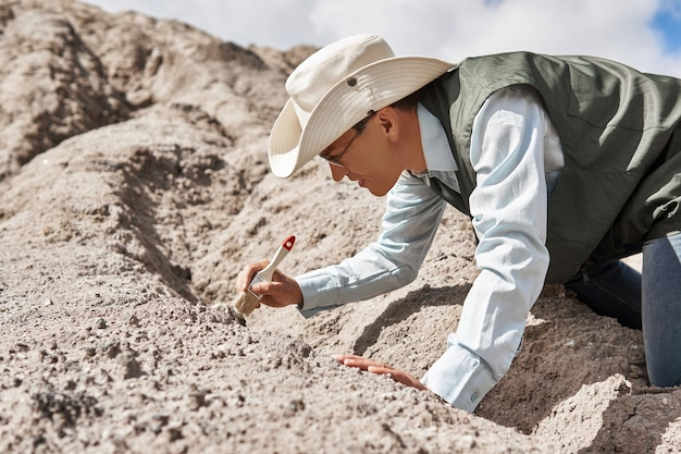 Мужчина-палеонтолог или археолог очищает находку щеткой в пустыне