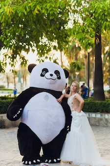 A man in a panda suit comforts an injured woman steps in the city