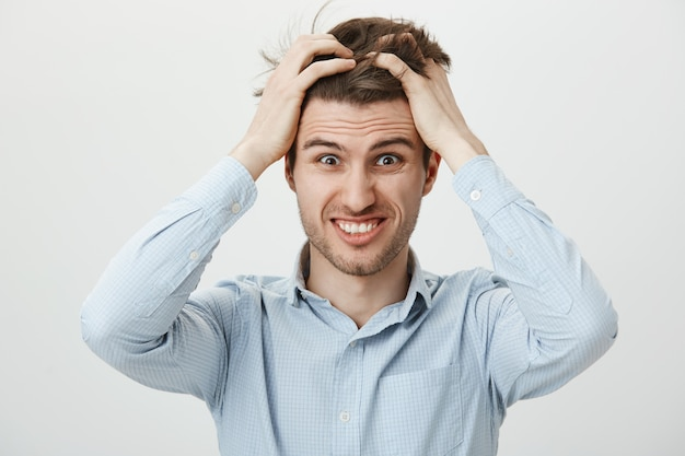 Man in panic feeling troubled, tossing hair alarmed