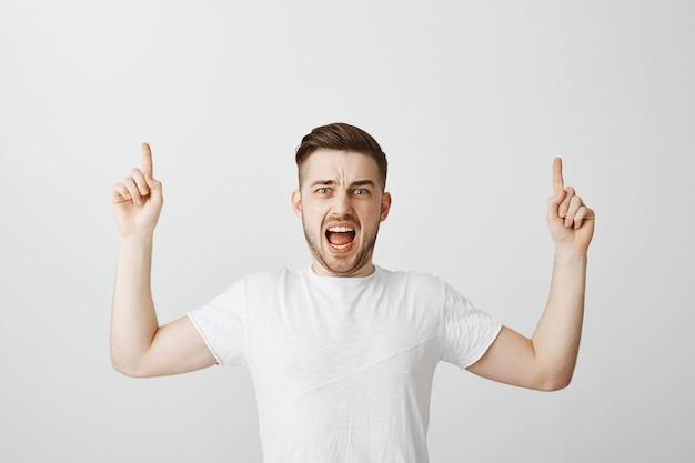 Uomo in preda al panico che grida e punta il dito verso l'alto