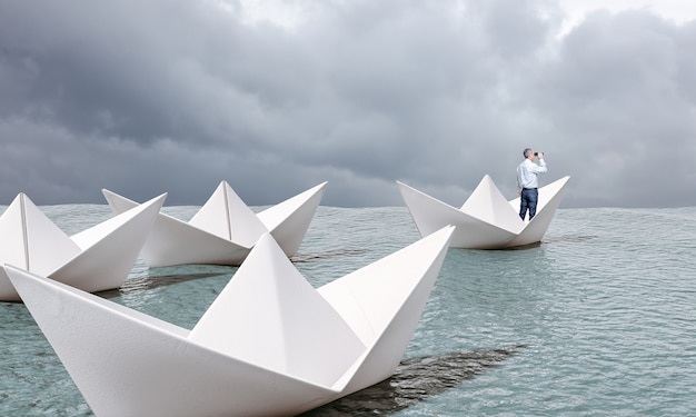 Man on paper boat with binoculars sailing on the sea.