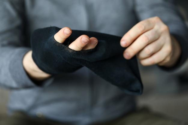 Человек передает пальцы через большую дыру в черном носке крупным планом
