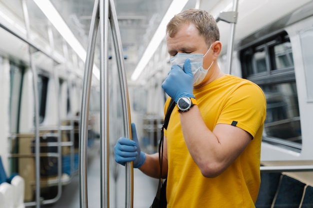 Man passenger coughs and has problems with breathing, wears disposable mask and gloves, stands in public transport