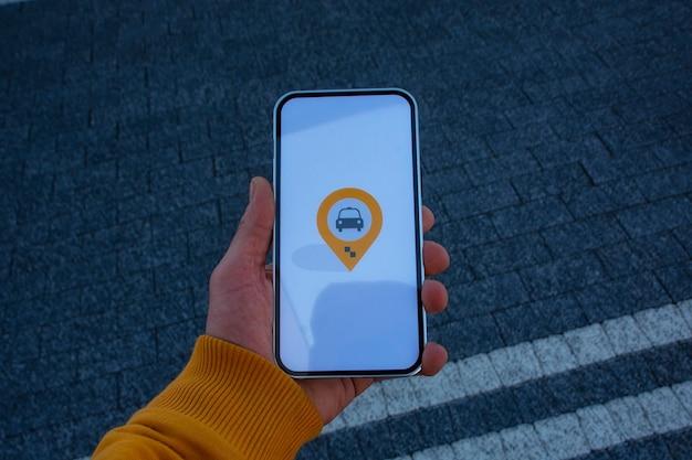 주차장에 있는 남자 승객은 모바일 애플리케이션이 있는 스마트폰을 들고 온라인으로 택시를 부릅니다.