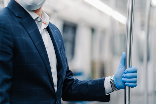 Man passenger wears protective medical glove from coronavirus, touches handrail in subway carriage, poses in public transport, dressed formally. virus, influenza, quarantine and health care concept