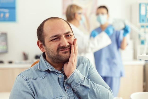 歯科矯正予約中に歯痛を訴える口腔病学キャビエントを訪れる男性患者
