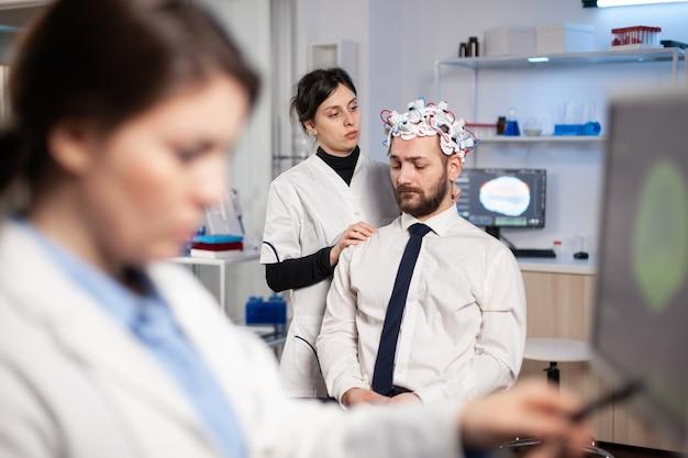 Мужчина-пациент ждет эксперимента с головным мозгом с гарнитурой в исследовательской лаборатории, в то время как ученый вносит изменения в клинику высоких технологий. невролог изучает нервную систему.
