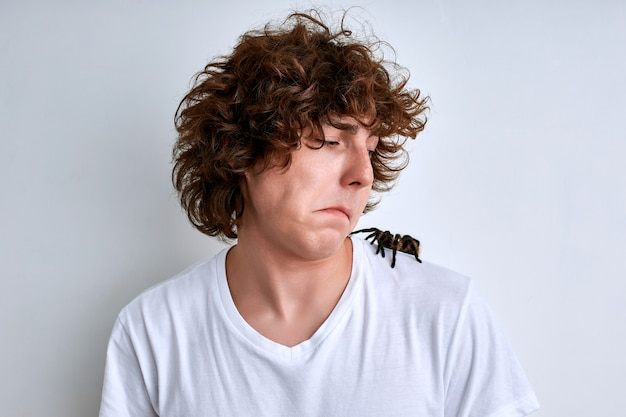 남자는 참을성있게 흰 벽에 고립 된 거미를 어깨에 기어 다니는 거미를 말합니다.