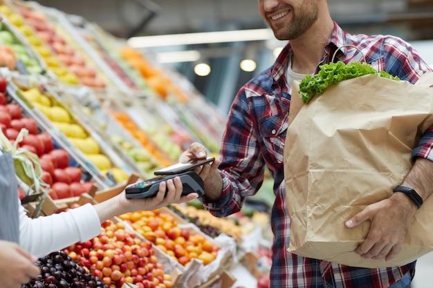Человек платит на смартфон в супермаркете