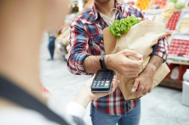 Человек, платящий smartwatch в супермаркете