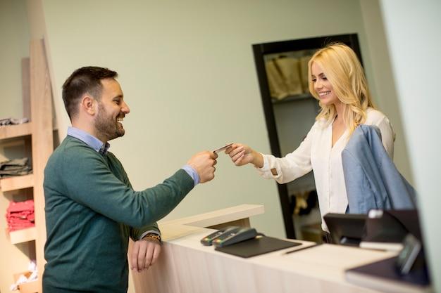 Мужчина платит женскому продавцу с помощью кредитной карты в магазине одежды