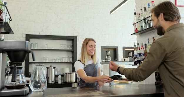 モダンなカフェのターミナルで非接触型スマートウォッチによるnfcテクノロジーで持ち帰り用のコーヒーを支払う男性。非現金支払いの概念。