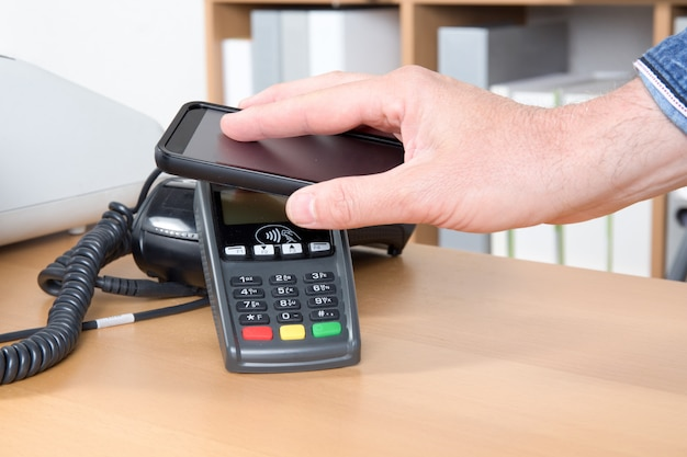 Man paying for good with nfc technology on mobile phone