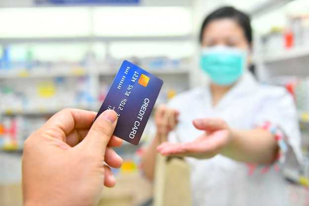 Man paying for medicaments with credit card in pharmacy drugstore