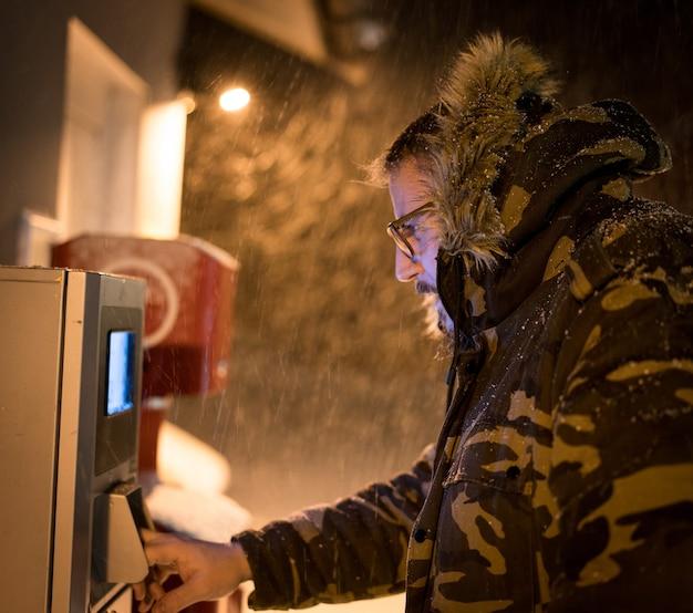 冬の嵐の中でサービスにお金を払っている男
