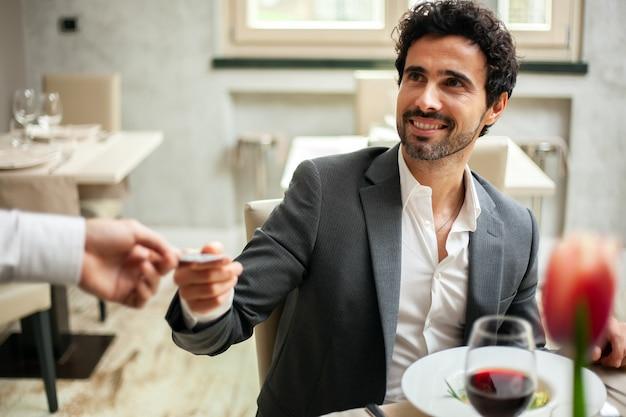 Человек оплачивает счет кредитной картой