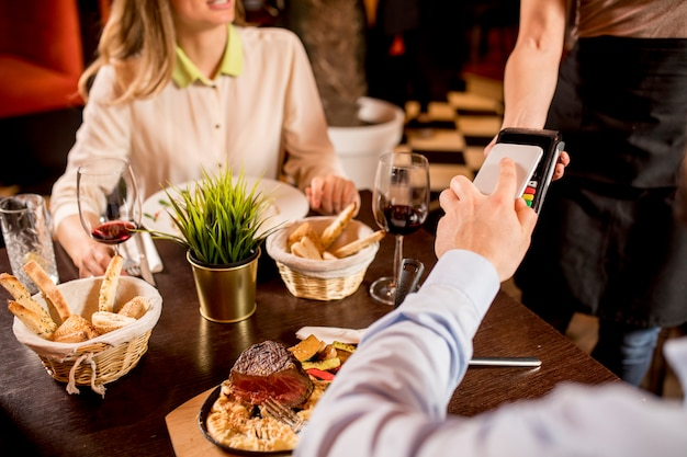 Man paying with nfc technology on mobile phone at the restaurant