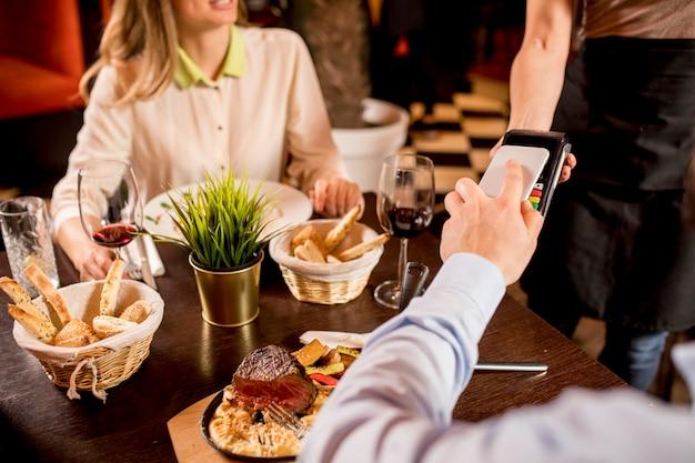 レストランで携帯電話でnfcテクノロジーで支払いをする男性