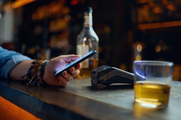 Мужчина платит по телефону у стойки бара, бесконтактная оплата. мужчина кладет смартфон к терминалу в пабе, современные безопасные технологии