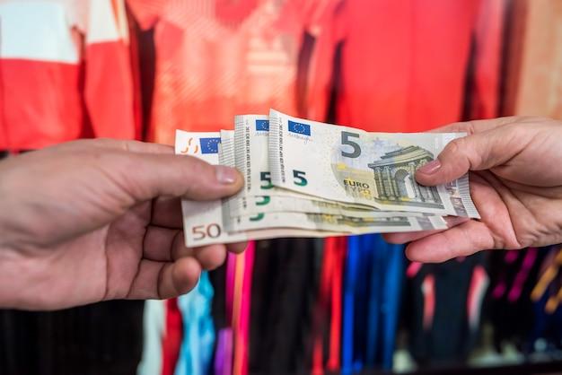 男は衣料品店で購入代金を支払います。ショッピング