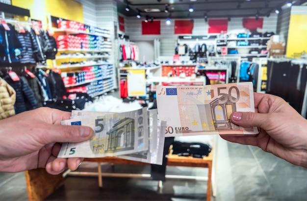남자는 옷가게에서 구매 비용을 지불합니다. 쇼핑