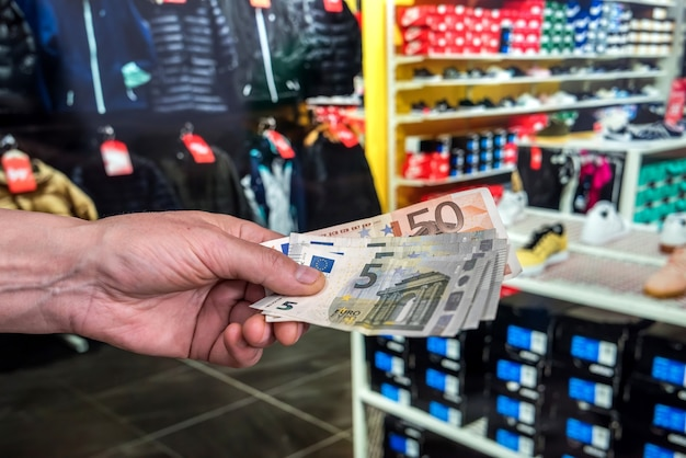 男は衣料品店の買い物で購入代金を支払う