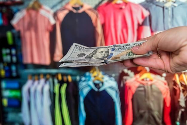 男は店で洋服を買うためにドルで支払います。ショッピングコンセプト
