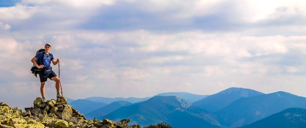 Man on peak of mountain. emotional scene. young man with backpack standing with raised hands on top of a mountain and enjoying mountain view. hiker on the mountain top. sport and active life concept.