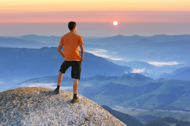 Man on peak of mountain