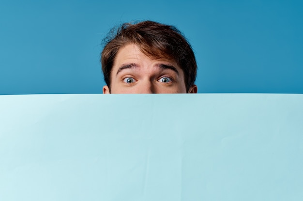 A man peeking out from behind a banner close-up advertising copy space marketing