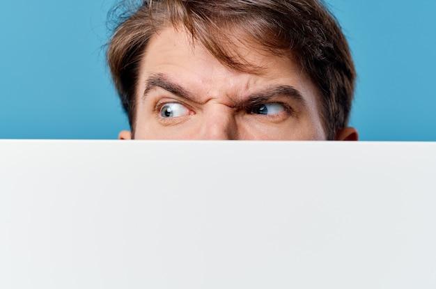 バリア広告の後ろから覗く男コピースペースブルークロップドビュー。