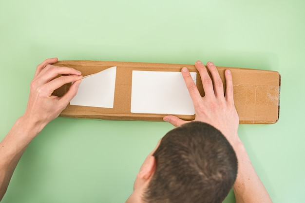 Man peels off the labels from a long paper parcel on a light green background.