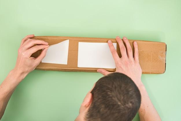 남자는 밝은 녹색 배경에 긴 종이 소포에서 레이블을 벗 깁니다.