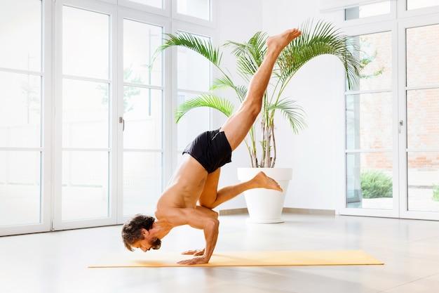 Man performing an eka pada bakasana yoga or one legged crane pose
