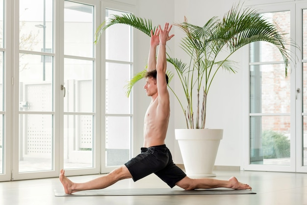 Man performing a hanumanasna or monkey yoga pose doing forward splits with arms raised in a high key gym with copyspace in a health and fitness concept