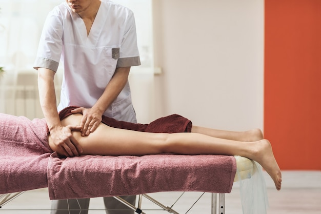 A man performing a massage on the thigh and gluteal muscles in his office