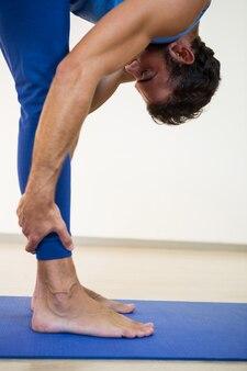 Man performing standing forward bend