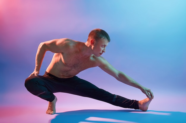 Man performing yoga, doing exercising for stretching