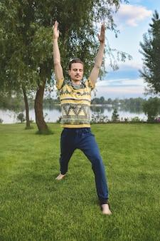 Человек, выполняющий йоги молодой фитнес-человек, открытый упражнения.