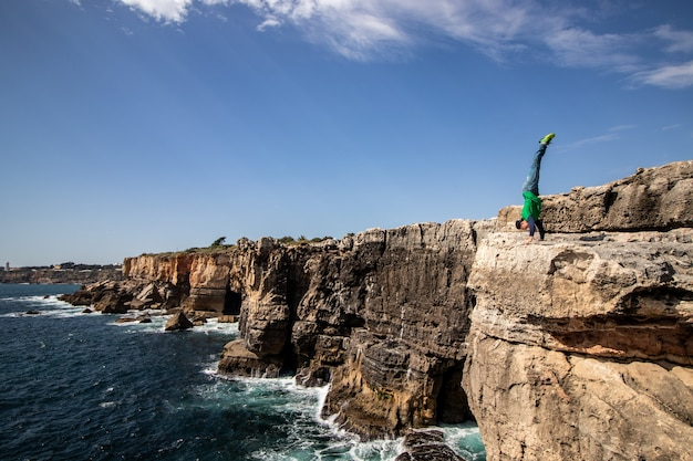 Man performs a handstand on the edge of cliff. concept of extreme, freedom and braves.