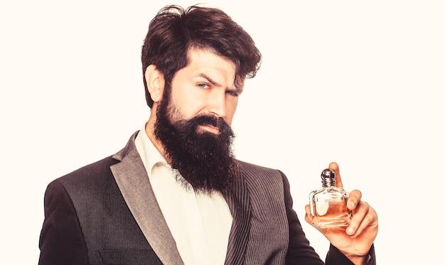 男の香水、香り。香水またはケルンのボトルと香水、化粧品、香りのケルンのボトル、ケルンを保持している男性。男性的な香水、スーツを着たひげを生やした男。香水のボトルを保持している男性
