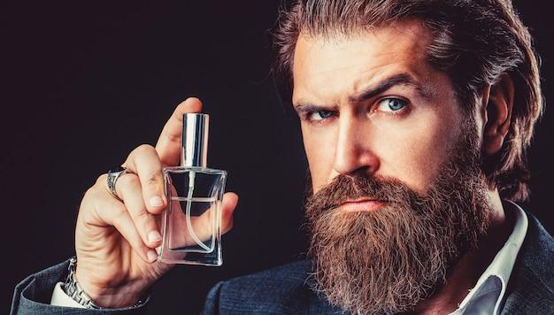 男の香水、香り。香水またはケルンのボトル、香水、化粧品、香りのケルンのボトル、ケルンを保持している男性。