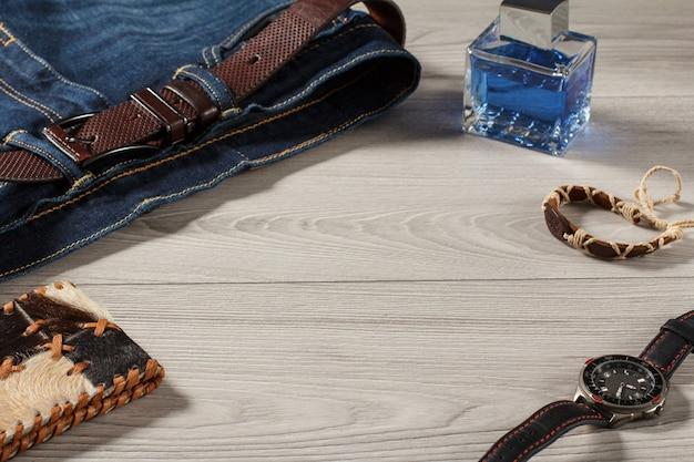 男性の香水、革のストラップ、灰色の木製の背景に革のベルト、お守り、革の財布とブルージーンズの時計